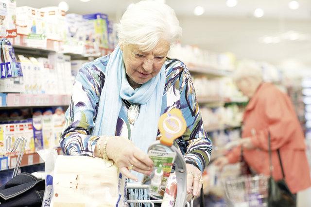 Sichtbarkeit verbessern: Eine ältere Kundin nutzt den angebotenen Service einer Lupe in einem Geschäft